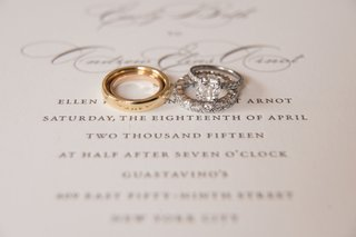 two-wedding-bands-one-gold-one-diamond-atop-couples-wedding-invitation-with-engagement-ring