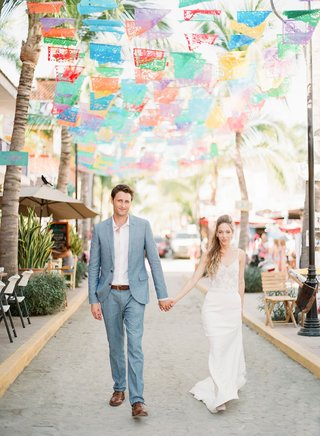 bride-in-spaghetti-strap-v-neck-wedding-dress-groom-in-grey-suit-light-blue-under-fiesta-flags-mexic