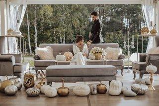 bride-in-wedding-dress-gold-silver-pumpkins-velvet-sofa-armchair-bench-white-flowers-candelabra