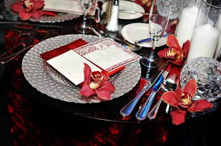 red-orchids-and-napkin-on-silver-charger-plates