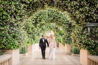 las-vegas-wedding-at-the-bellagio-bride-and-groom-portrait-under-arches-of-greenery-white-blooms