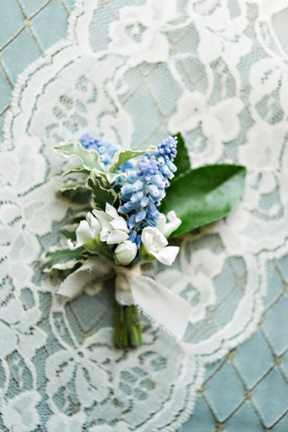 white-flower-blue-flower-green-leaves-boutonniere-tied-with-white-ribbon-on-lace