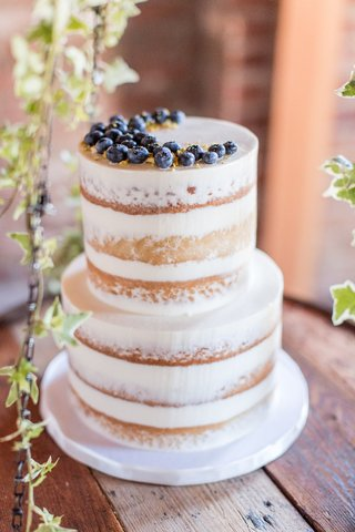 semi-naked-wedding-cake-blueberries-and-gold-details-vanilla-almond-pistachio-crumbs-on-wood