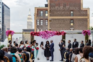 bride-and-groom-under-archway-female-officiant-book-bindery-empire-state-building-rooftop