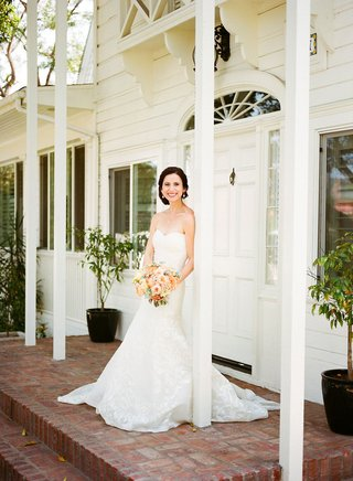 bride-at-lombardi-house-updo-strapless-carolina-herrera-wedding-dress-peach-bouquet-flowers-brick