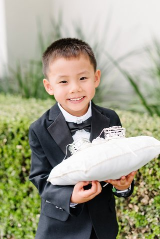 asian-american-ring-bearer-boy-holding-ring-pillow-for-wedding-ceremony-at-catholic-church