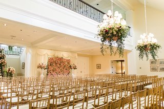 wedding-ceremony-in-grand-hall-of-club-gold-chairs-flower-wall-flower-chandeliers