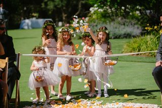 flower-girls-in-blush-dresses-and-greenery-flower-crowns-throw-petals-outside-aisle