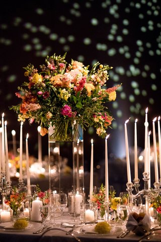 wedding-reception-with-tall-taper-candles-and-flower-arrangement-with-pink-yellow-and-orange-flowers