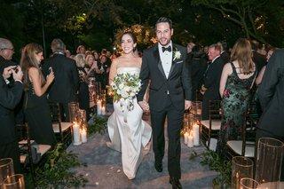 bride-in-strapless-oscar-de-la-renta-wedding-dress-groom-in-tuxedo-bow-tie-walking-up-aisle-night