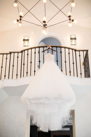 monique-lhuillier-ball-gown-with-lace-and-tulle-on-hanger-hanging-from-balcony-before-staircase