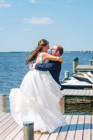 bride-in-striped-hayley-paige-wedding-dress-with-groom-in-navy-suit-on-private-dock