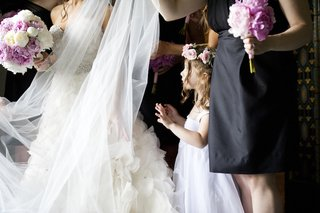 flower-girl-in-white-dress-with-thick-straps-and-pink-rose-crown-looks-at-bride-in-strapless-lazaro
