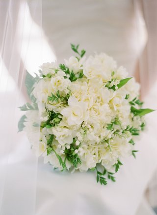 classic-wedding-bouquet-with-white-flowers-roses-lily-of-the-valley-and-greenery-behind-veil