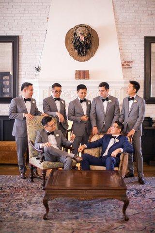 groomsmen-in-grey-in-lounge-surrounding-groom-in-navy-sitting-in-vintage-chair