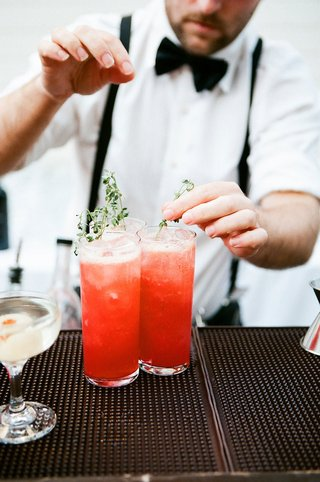 wedding-reception-cocktail-hour-bartender-putting-fresh-herbs-in-red-cocktail-ice-highball-glass