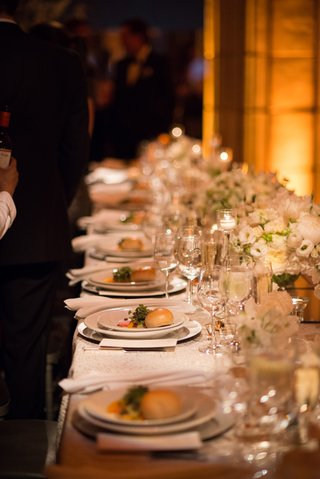 a-long-reception-table-with-white-china-and-low-white-floral-arrangements-with-food