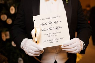 man-in-white-gloves-holding-formal-ceremony-program-white-stationery-and-black-calligraphy-ribbon