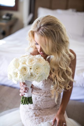 bride-with-long-blonde-hair-curls-galia-lahav-wedding-dress-bridal-suite-sniffs-bouquet-white-roses