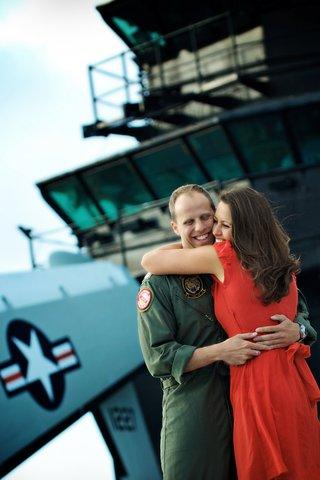 woman-in-red-dress-hugs-man-in-u-s-navy-jumpsuit-flight-uniform