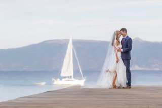 bride-groom-pose-dock-lake-tahoe-sailboat-long-veil-blue-suit-purple-tie