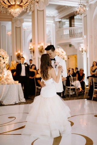 bride-in-wedding-dress-trumpet-gown-white-tuxedo-jacket-groom-gold-monogram-dance-floor-chandelier
