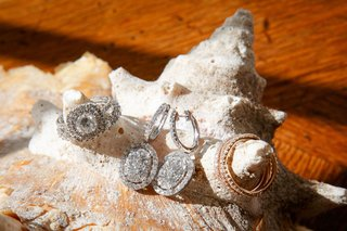 double-halo-engagement-ring-with-halo-earrings-and-rose-gold-wedding-rings-on-conch-shell