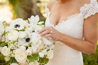 bride-in-v-neck-lace-cap-sleeve-romona-keveza-wedding-dress-holding-white-anemone-ranunculus-bouquet