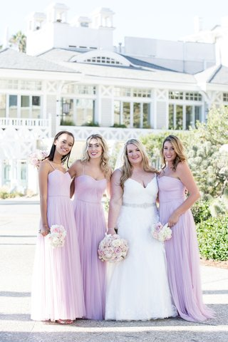 bride-in-v-neck-ball-gown-with-silver-sash-and-bridesmaids-in-pink-lavender-purple-gowns-blush