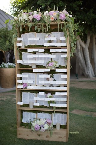garden-wedding-reception-with-place-cards-displayed-on-bookcase-with-white-purple-peach-flowers