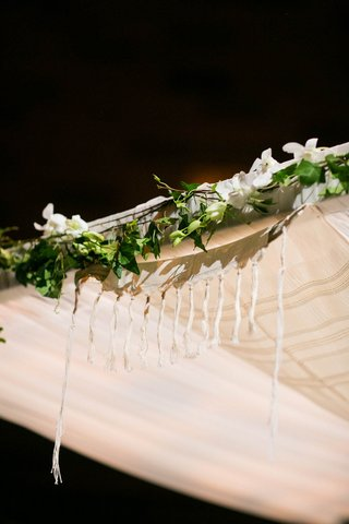 tallit-at-jewish-wedding-ceremony-on-top-of-chuppah-with-green-garland-and-white-flowers