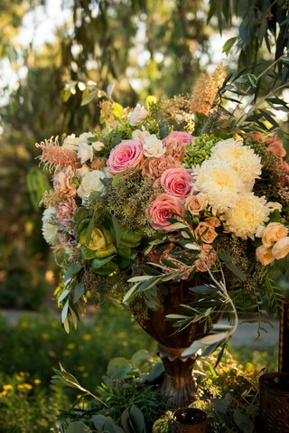 a-cluster-of-pink-white-and-green-flowers-and-leaves-in-gold-vase-outside-couples-ceremony-space