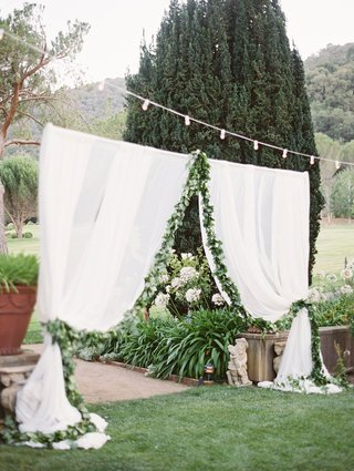 sheer-white-curtain-entrance-to-outdoor-reception-space-lined-with-foliage-below-string-of-lights