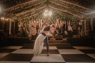 wedding-photo-of-bride-in-keyhole-back-wedding-dress-dip-string-lights-checkerboard-dance-floor