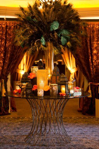 moroccan-style-engagement-party-table-with-gold-vase-of-peacock-feathers-lanterns-with-candles