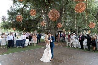 saddlerock-ranch-wedding-outdoor-reception-wooden-outdoor-dance-floor-first-dance-twinkle-lights