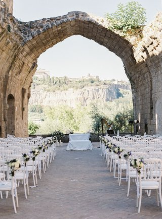 xii-century-benedictine-abbey-hotel-countryside-view-umbria-italy-stone-ruins-white-chairs-purple