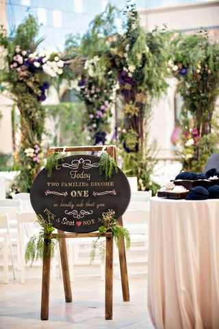 chalkboard-ceremony-sign-on-easel-with-greenery-accents