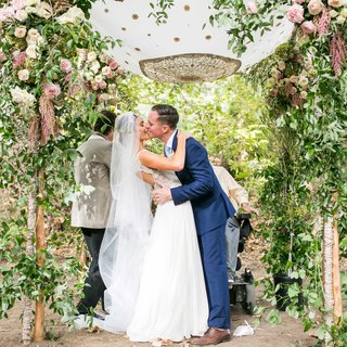 bride-in-maradee-wahl-veil-and-groom-in-navy-blue-tie-kiss-under-pretty-garden-chuppah-outside-pink