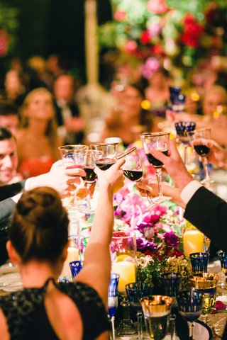 wedding-guests-at-tent-wedding-cheers-and-toast-with-gold-rim-wine-goblets