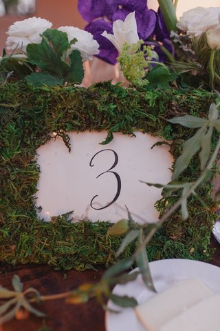 white-and-black-table-number-in-grass-frame