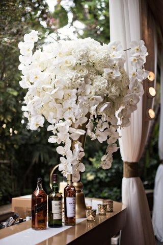 outdoor-bar-area-for-cocktail-hour-gold-riser-white-orchid-rose-hydrangea-flowers-alcohol-candles