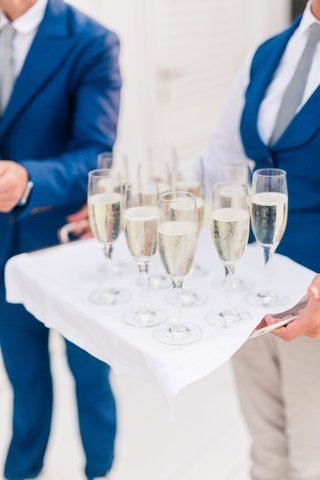 glasses-of-prosecco-on-silver-tray-draped-with-white-fabric