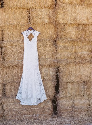 monique-lhuillier-wedding-dress-hanging-on-hay-stack