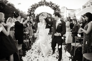 black-and-white-photo-of-bride-in-classic-wedding-dress-with-groom-flower-petal-toss-recessional