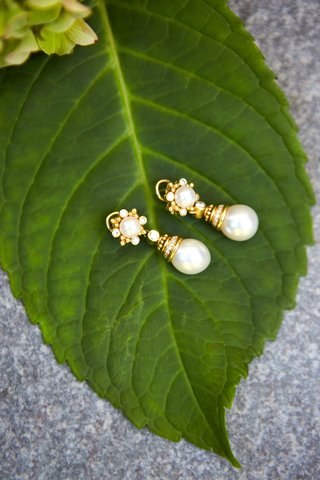 classic-wedding-jewelry-yellow-gold-drop-earrings-with-pearls-and-diamonds-on-green-leaf-detail-shot