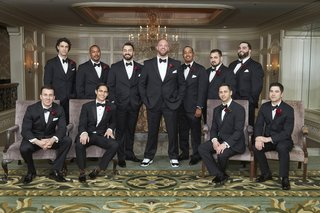 groom-and-groomsmen-black-tuxedos-groom-in-sneakers-groomsmen-in-dress-shoes