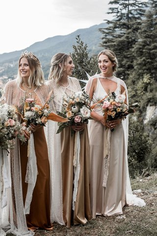 bridesmaids-at-lake-como-wedding-ceremony-boho-chic-style-earth-colored-dresses-long-capes-bouquets