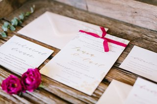 wedding-invitation-white-stationery-and-gold-foil-calligraphy-text-hot-pink-ribbon-bougainvillea