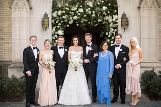 wedding-portrait-groom-with-family-and-bride-mother-of-bride-in-blue-dress-long-sleeves-church-arch